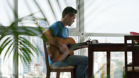 Portrait Of Happy Man Playing Guitar And Singing At Home Archivo
