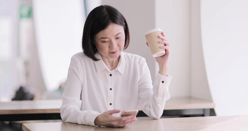 Businesswoman in a café using a smartphone Live Action