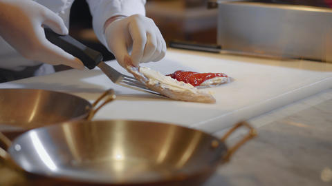 Chef hands prepare fish fillet over cutting board. Food preparation in modern Live Action