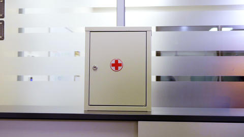 first aid kit box with red cross on shelf in modern office Footage