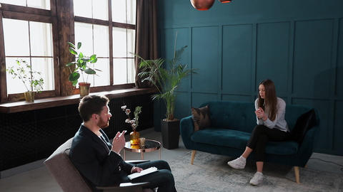 Young woman visiting male psychologist sitting on the comfortable couch during Footage