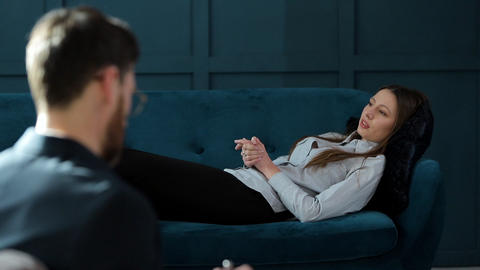 Young woman visiting male psychologist lying on the comfortable couch during Live Action