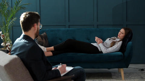 Young woman visiting male psychologist lying on the comfortable couch during Footage