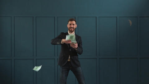 Young happy businessman dancing and throwing money. Slow motion. Successful Footage
