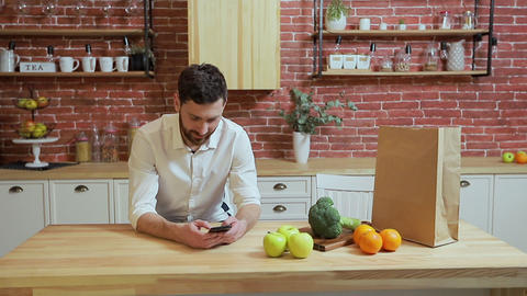 Man browsing on mobile phone at home kitchen. Handsome young man browsing on Live Action