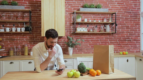 Man browsing on mobile phone at home kitchen. Handsome... Stock Video Footage