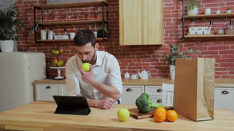 Man browsing on tablet PC at home kitchen. Handsome young man browsing on Tablet Live Action