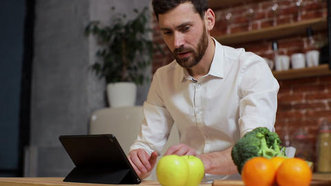 Man browsing on tablet PC at home kitchen. Handsome young man browsing on Tablet Footage
