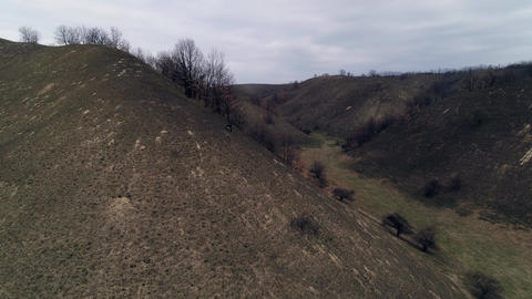 Flight through hilly landscape. Burnt grass. Camera ascendingm reveals landscape Footage