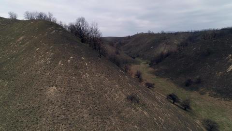 Flight through hilly landscape. Burnt grass. Camera ascendingm reveals landscape Live Action