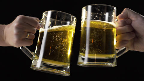 Clinking beer mugs with light golden beer in slow motion, drinking beer with Live Action