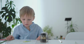 A small child sitting at the table draws a pencil drawing painting in different Footage
