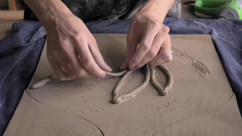 ceramist lays out a pattern on the future vase for flowers, dolly shot Footage