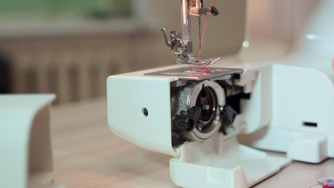 Close-up, hands of a seamstress take out threads for a bobbin. Slow motion Live Action