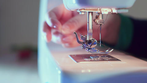 Extra close-up, sewing needle on the machine, the hand of the seamstress inserts Live Action