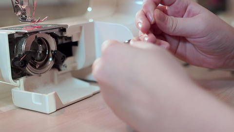 Close-up, hands of a seamstress are preparing a bobbin for a sewing machine Live Action