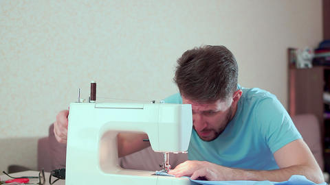 A man runs a sewing machine. Workplace at home Stock Video Footage