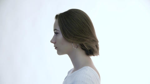 Profile of a young beautiful woman on a white background Dreamily raises her Live Action