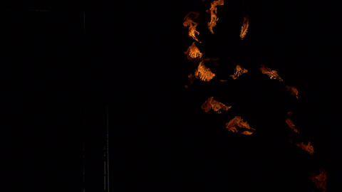 Decorative fiery torches in the hands of fakirs form figures of flame on a black GIF