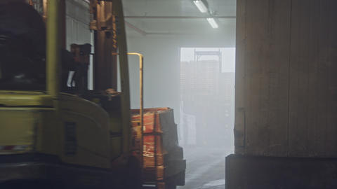 Forklift lifting pallets in a dark cooled warehouse Archivo
