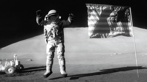 Astronaut jumping on the moon and saluting the American flag. Some Elements of GIF
