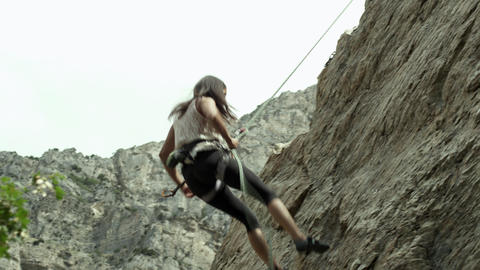 Woman rappelling down rock cliff Footage