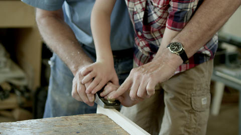 Grandfather teaching a boy how to use a wood plane. In a wood shop Live Action