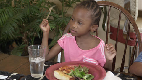 Young girl eating dinner at dinning room table Footage