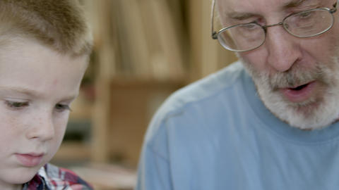 Tight shot of grandfather and grandson as they work in a wood shop Footage