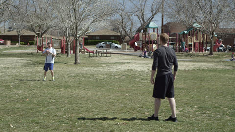 Son and father playing catch with a football in the park Footage