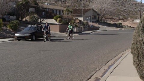 Man and woman riding bikes in the neighborhood Live Action