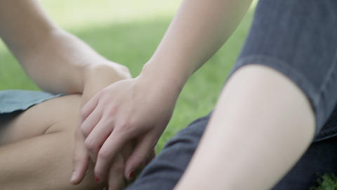 Teenage girl holds boy's hand while sitting on the grass Footage
