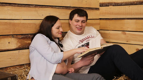Pregnant woman and her husband reading book Live Action