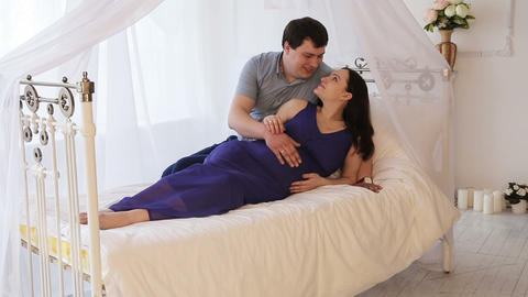 Pregnant woman with her husband on the bed Live Action