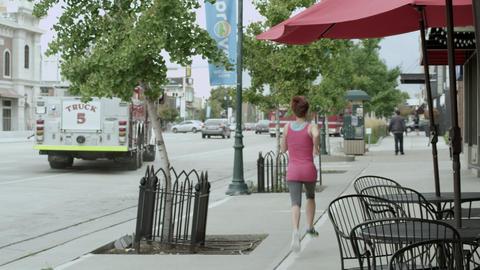Firetruck leaving as woman runs by on sidewalk Footage