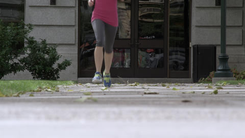 Low angle shot of a a woman jogging toward the camera Footage