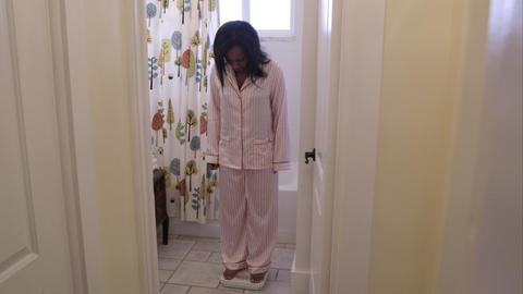 Pajamaed woman in bathroom weighing herself Footage