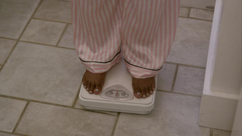 Tight shot of a woman's feet as she weighs herself in the bathroom Footage