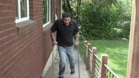 Man walking up home ramp with crutches Footage