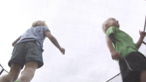 Three kids jumping on a trampoline, angle from underneith Live Action