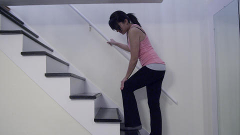 Woman in athletic clothes and knee pain walking up home stairs Footage
