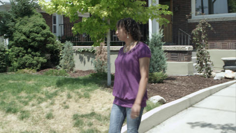Woman leaving home and starting to walk down the sidewalk Footage