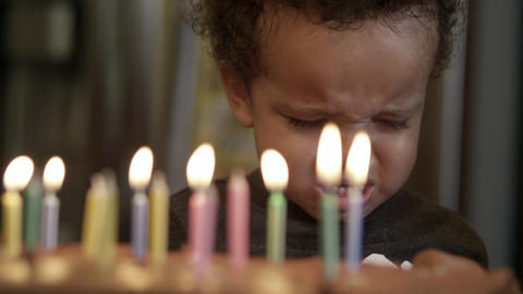 Young boy crys after he burns himself on birthday candle. His mother tries to co Footage