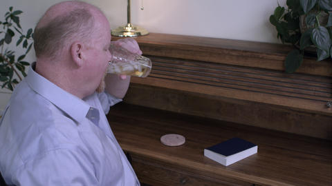 Man at a desk drinking liquor, then looking at an Alcoholics' Anonymous book Live Action