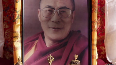 Slowly tilting down shot of a portrait of the Dalai Lama Footage