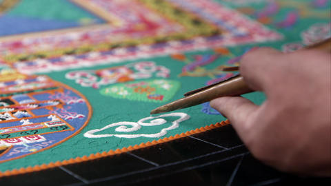Tight shot of someone adding sand to a colorful sand mandala Footage