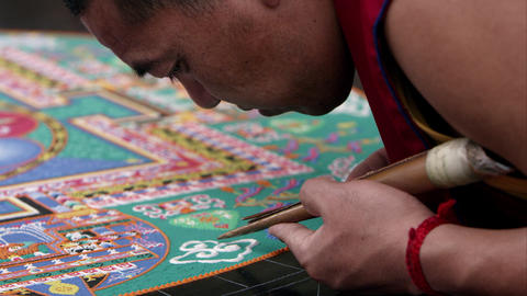 Shot of a man carefully adding sand to a sand mandala Footage
