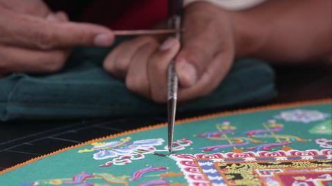 Tight shot of a man carefully adding sand to a symbolic sand mandala Footage