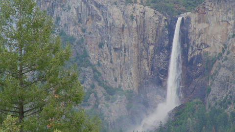 Mist from Yosemite falls blows along canyon Footage
