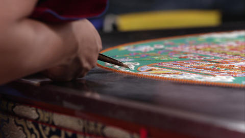 Tight shot of a man adding sand to a very colorful sand mandala Footage